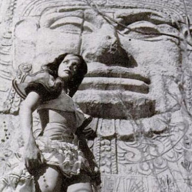 Burnu Acquanetta posing in a Mexican costume in front of a fake Olmec head